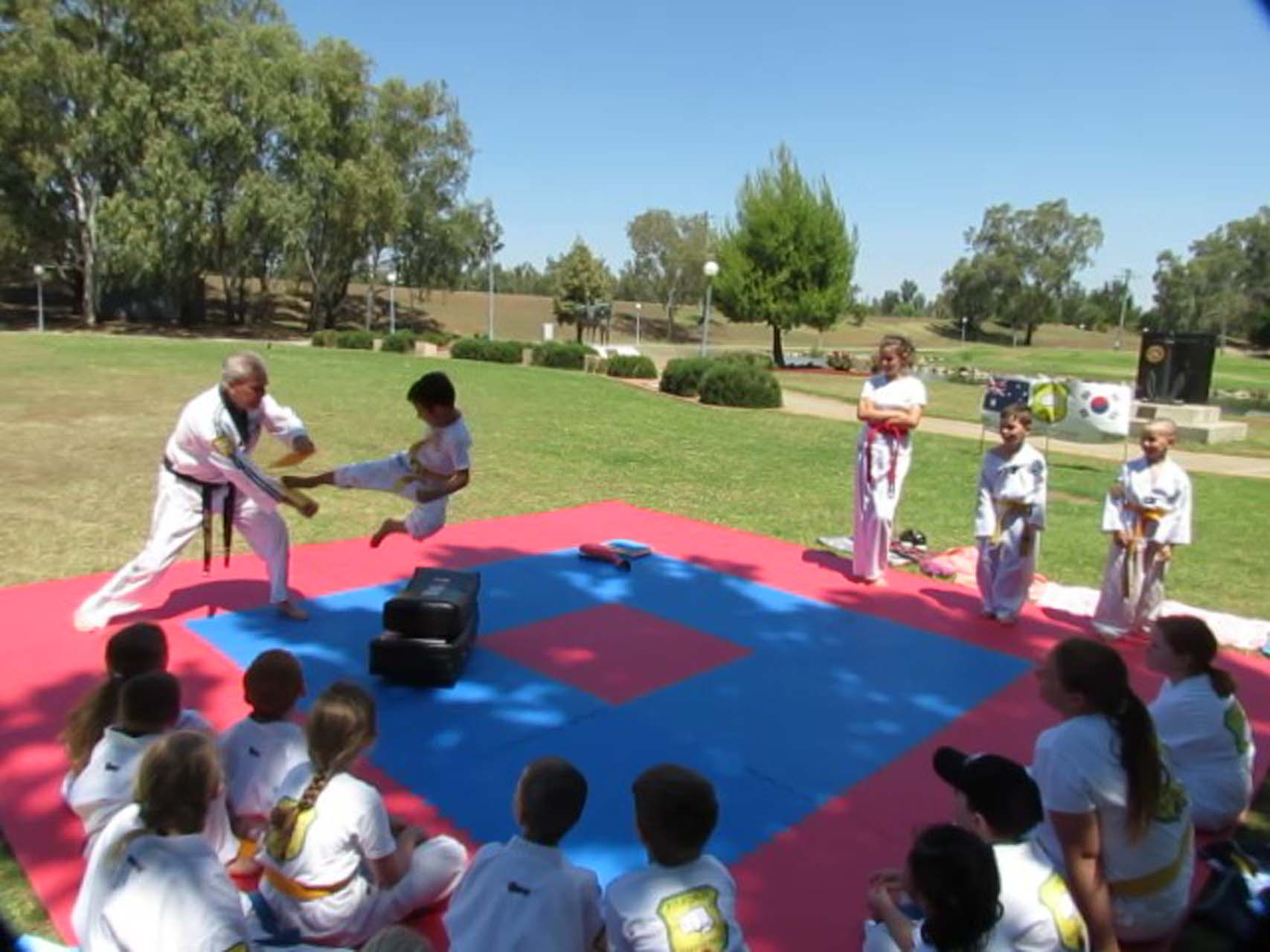 Young taekwondo students in Tamworth practicing martial arts on a red and white rubber mat.