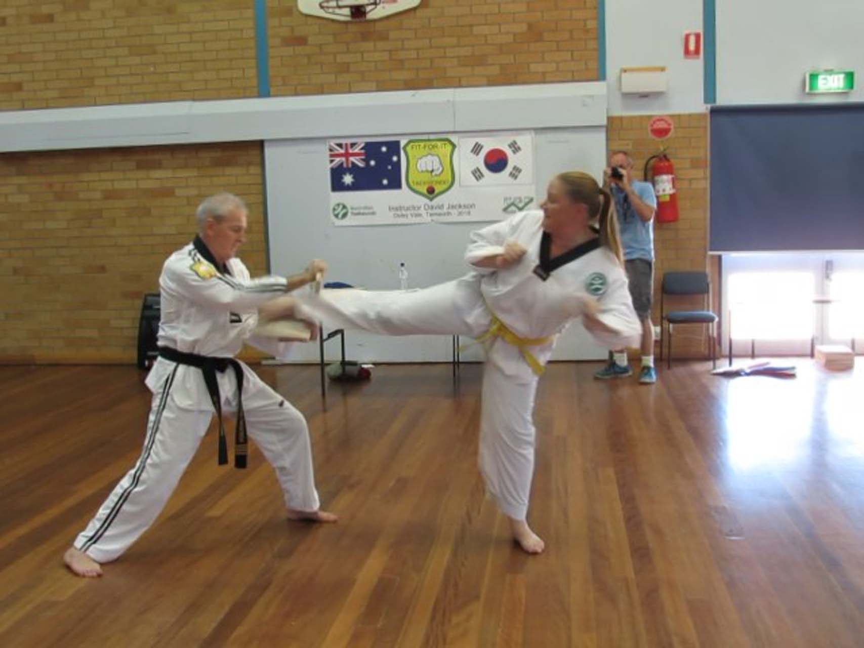 A young female adult using her taekwondo skills to kick a board from between the hands of an old man.