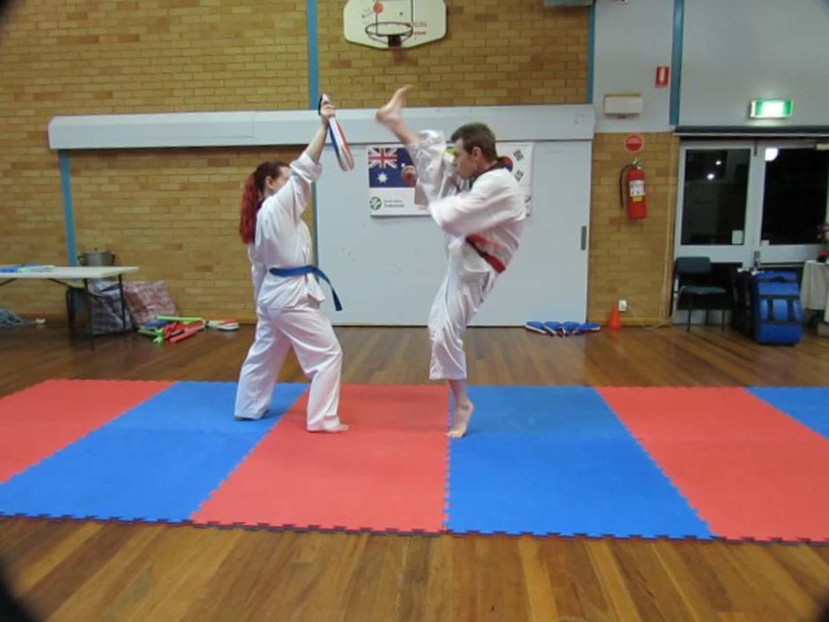 A woman helps a man practice his taekwondo high kick at Martial Arts Tamworth.