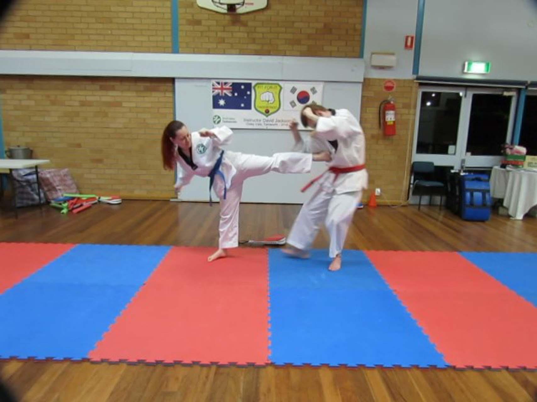 A woman taekwondo kicks a man in the stomach at Martial Arts Tamworth.