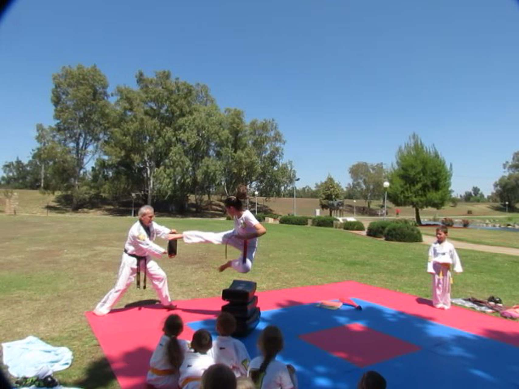 A young female taekwondo student flys through the air at her instructor.