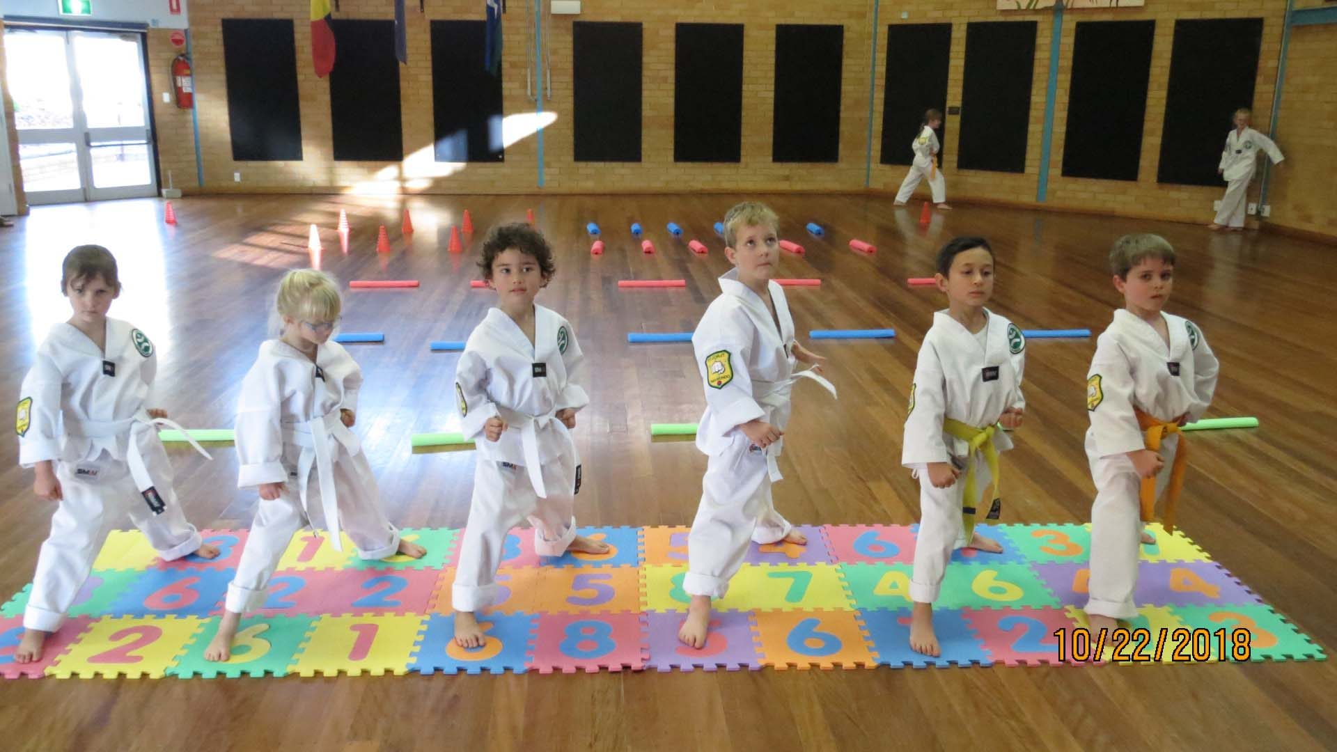 6 young taekwondo students practice martial arts inside a Tamworth gymnasium.