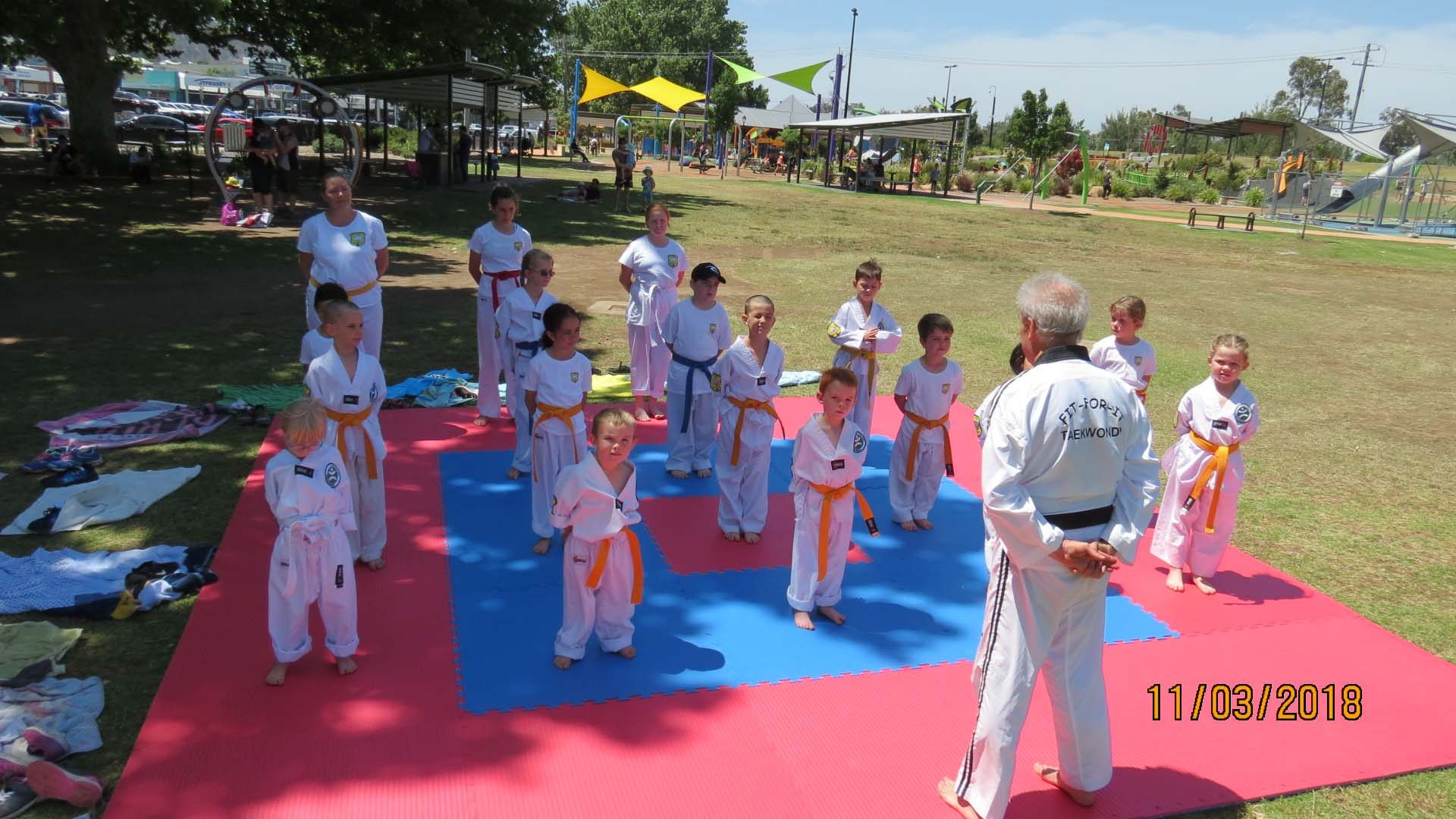 Young martial arts students ready to practice taekwondo on a mat in Tamworth.