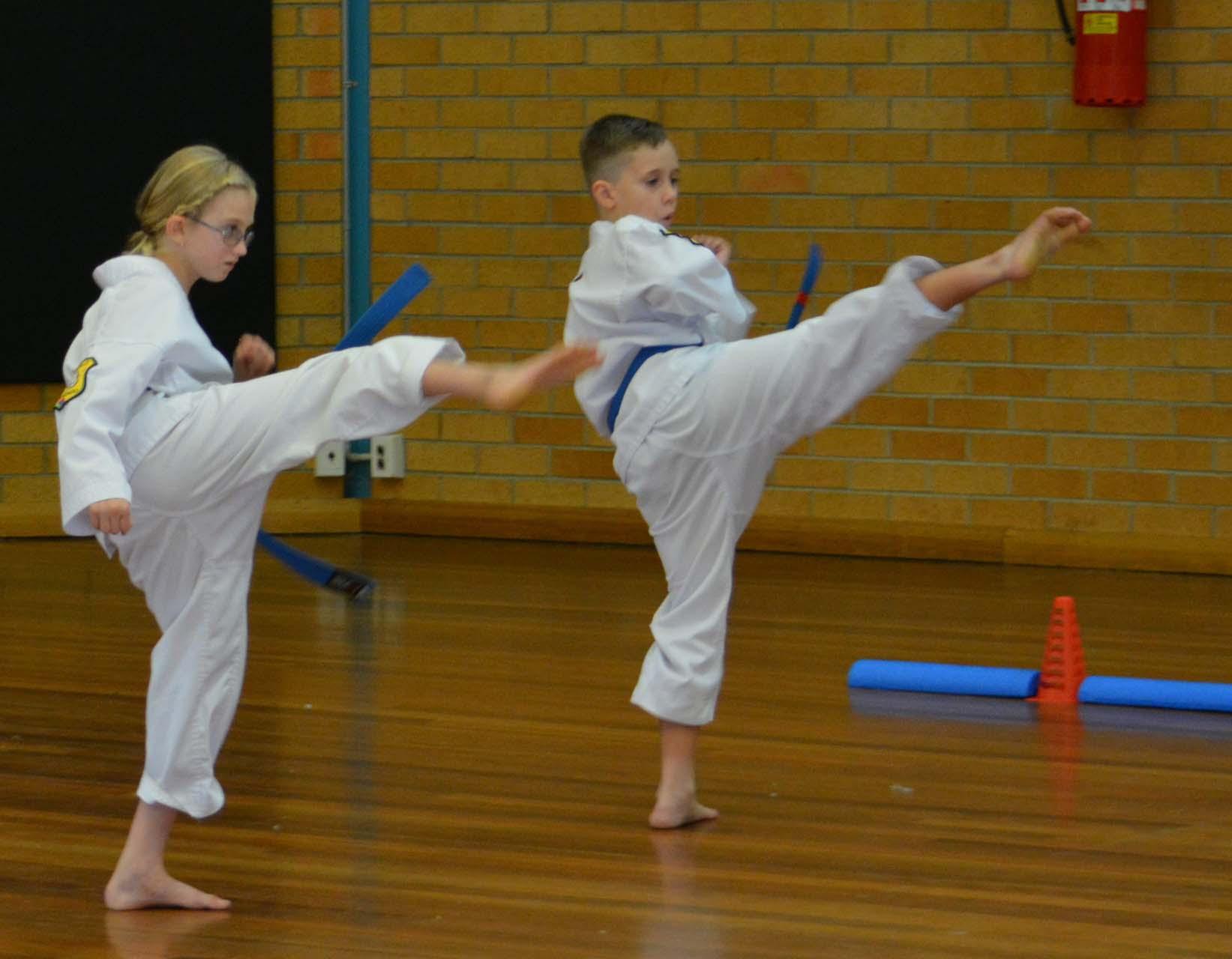 Two blue belt martial arts students practicing their high kicks at Tamworth martial arts.