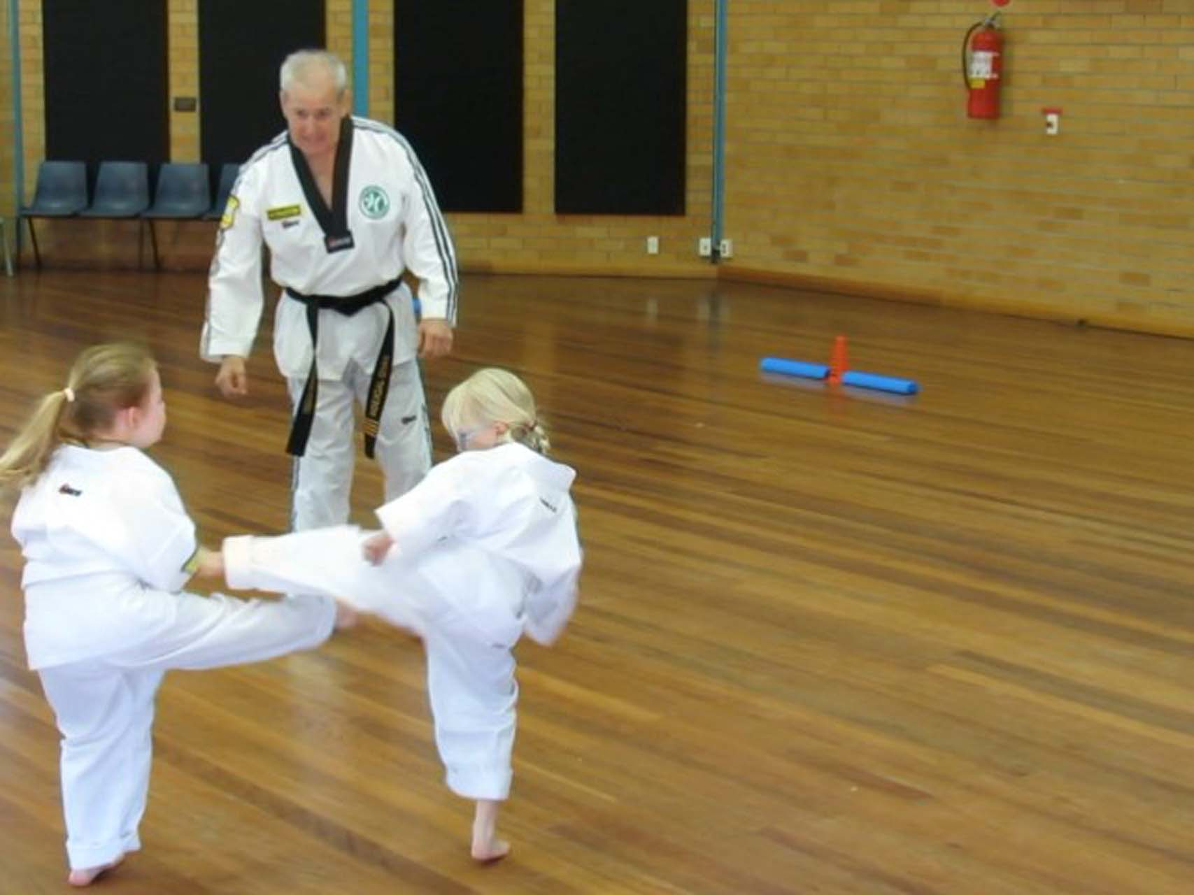 Two young martial arts girls practicing kicks in a taekwondo class in Tamworth.