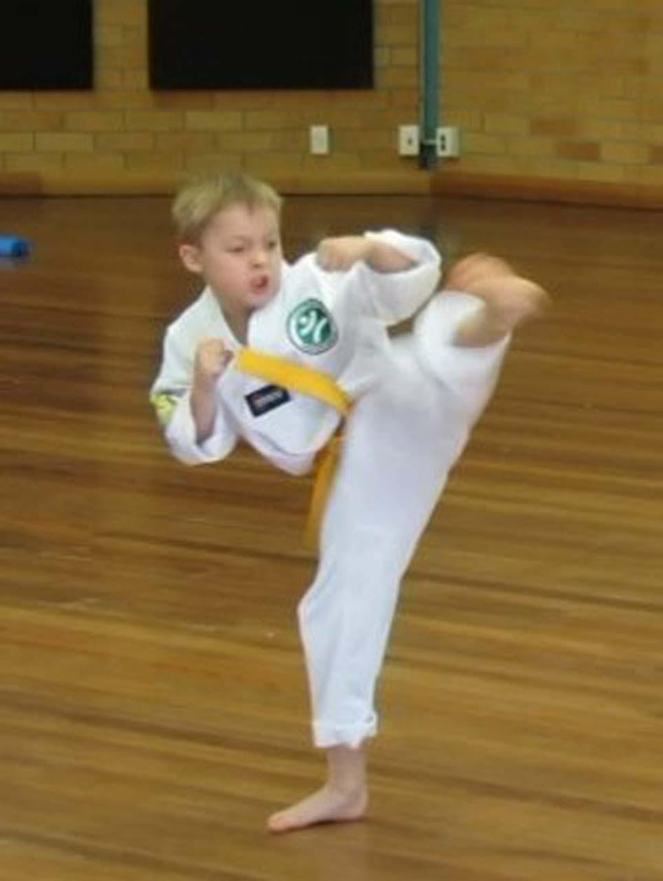 A young student of taekwondo practices a high kick at Tamworth Martial Arts