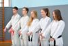 A group of young martial artists practice their Taekwondo lessons in front of an instructor.